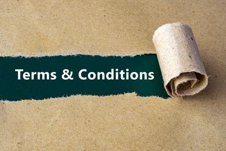 """Gescheurd bruin papier op groene ondergrond met """"Algemene Voorwaarden"""" woorden."""
