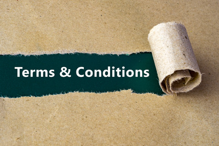 Torn brown paper on green surface with Terms & Conditions words. Stock Photo