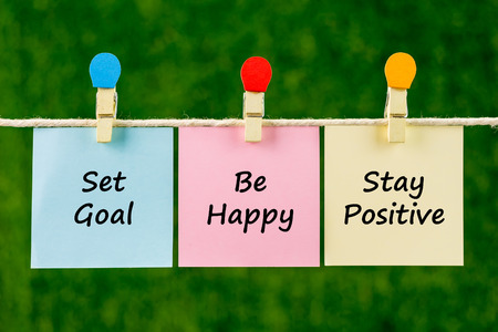 stay in the green: Word quotes of Set Goal, Be Happy, Stay Positive on sticky color papers hanging on rope against blurred green background.