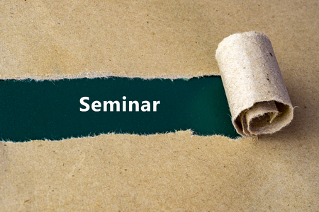 hint: Torn brown paper on green surface with Seminar word. Stock Photo
