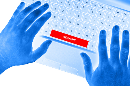 adware: Hands on laptop with ADWARE word on spacebar button. Stock Photo