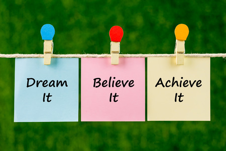 Word quotes of Dream It, Believe It, Achieve It on sticky color papers hanging on rope against blurred green background. Stock Photo