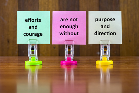 efforts: Word quotes of EFFORTS AND COURAGE ARE NOT ENOUGH WITHOUT PURPOSE AND DIRECTION on colorful sticky papers against wooden textured background.