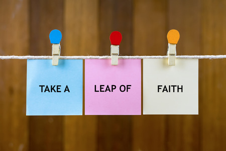 Word quotes of TAKE A LEAP OF FAITH on colorful sticky papers hanging by a rope against blurred wooden background. Stock Photo