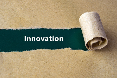 innovation word: Torn brown paper on green surface with Innovation word. Stock Photo