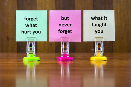 taught: Word quotes of FORGET WHAT HURT YOU BUT NEVER FORGET WHAT IT TAUGHT YOU on colorful sticky papers against wooden textured background.