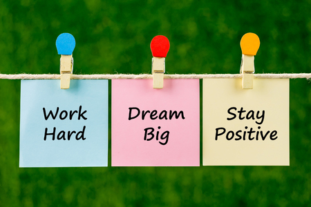 Word quotes of Work Hard, Dream Big, Stay Positive on sticky color papers hanging on rope against blurred green background. Imagens