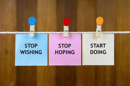 Word quotes of STOP WISHING, STOP HOPING, START DOING on colorful sticky papers hanging by a rope against blurred wooden background.