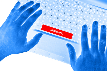 spamming: Hands on laptop with SPAMMING word on spacebar button. Stock Photo