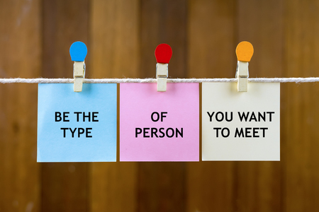 justify: Word quotes of BE THE TYPE OF PERSON YOU WANT TO MEET on colorful sticky papers hanging by a rope against blurred wooden background. Stock Photo