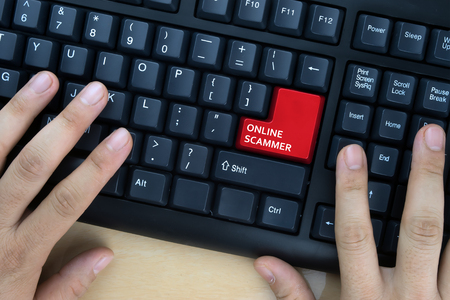 scammer: Hands on computer keyboard with Online Scammer words at enter button. Stock Photo