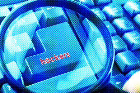 cyber terrorism: Magnifying glass on keyboard with Hackers word on button. Color halftone effect applied.