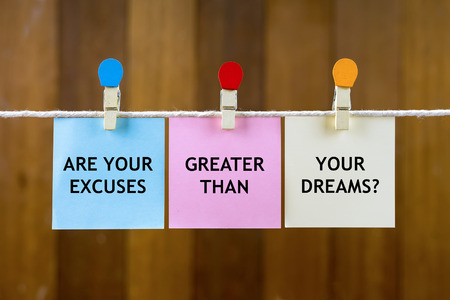 justify: Word quotes of ARE YOUR EXCUSES GREATER THAN YOUR DREAMS? on colorful sticky papers hanging by a rope against blurred wooden background.