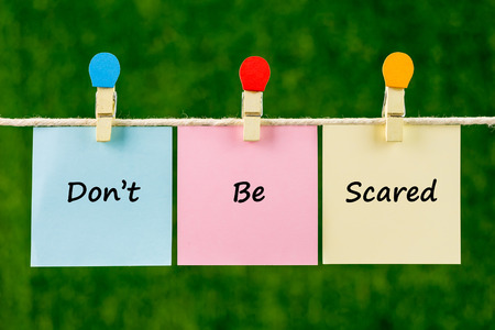 Words of Dont Be Scared on sticky color papers hanging by a rope against blurred green background.