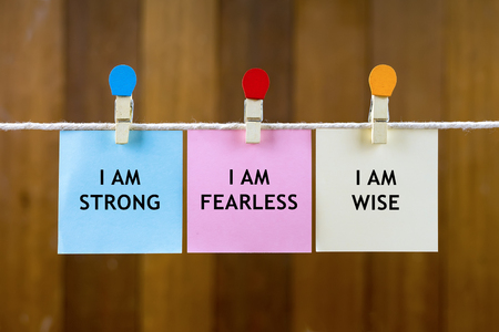 Word quotes of I AM STRONG, I AM FEARLESS, I AM WISE on colorful sticky papers hanging by a rope against blurred wooden background.