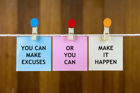 Word quotes of YOU CAN MAKE EXCUSES OR YOU CAN MAKE IT HAPPEN on colorful sticky papers hanging by a rope against blurred wooden background. Stock Photo