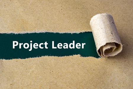 """lider: Rasgado de papel marrón en la superficie verde con las palabras """"Líder del Proyecto""""."""