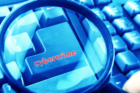 cyber terrorism: Magnifying glass on keyboard with Cybercrime word on button. Color halftone effect applied.