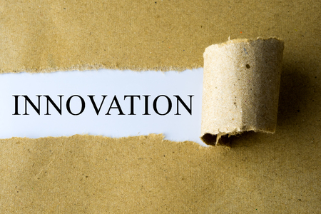 innovation word: Torn brown paper with INNOVATION word.