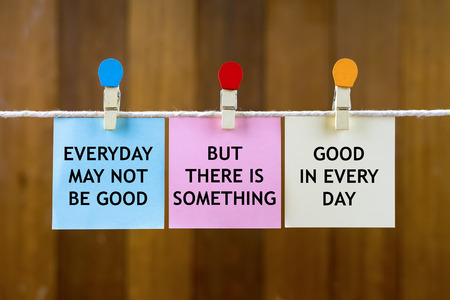 Word quotes of EVERYDAY MAY NOT BE GOOD, BUT THERE IS SOMETHING, GOOD IN EVERY DAY on colorful sticky papers hanging by a rope against blurred wooden background.