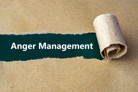 anger management: Torn brown paper on green surface with Anger Management words.