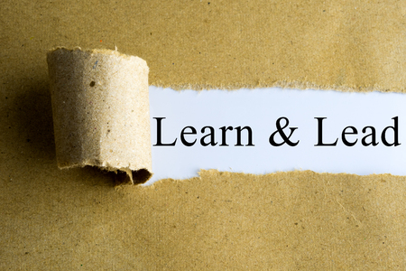 learn and lead: Torn brown paper with Learn & Lead words. Stock Photo