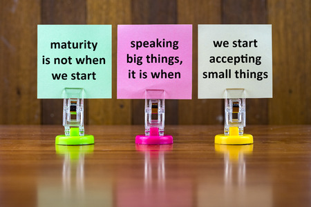 Word quotes of MATURITY IS NOT WHEN WE START TALKING BIG THINGS,ITS WHEN WE START ACCEPTING SMALL THINGS on colorful sticky papers against wooden textured background.