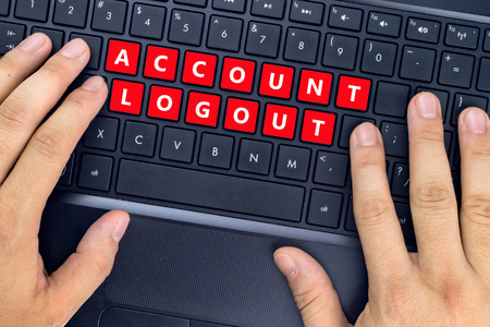 Hands on laptop with ACCOUNT LOGOUT words on keyboard buttons.