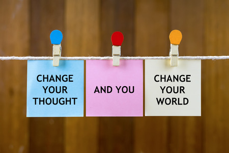 Word quotes of CHANGE YOUR THOUGHT, AND YOU, CHANGE YOUR WORLD on colorful sticky papers hanging by a rope against blurred wooden background.