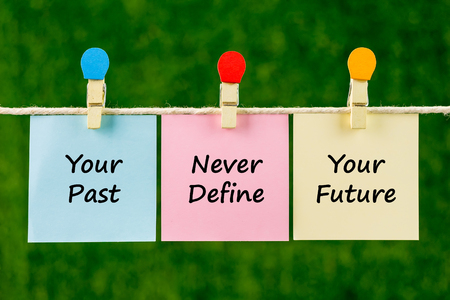 define: Word quotes of Your Past Never Define Your Future on sticky color papers hanging on rope against blurred green background.