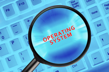 looking through an object: Magnifying glass on computer keyboard with Operation System words. Stock Photo