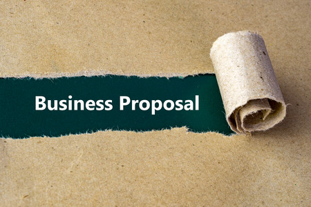 recommendations: Torn brown paper on green surface with Business Proposal words.