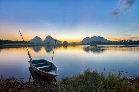 december sunrise: TIMAH TASOH PERLIS, MALAYSIA - DECEMBER 26,2015 : Beautiful reflection of sunrise with a boat by the lakeside in a summer day.