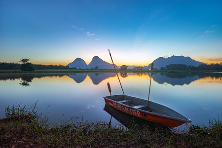 TIMAH TASOH PERLIS, MALAYSIA - DECEMBER 26,2015 : Beautiful reflection of sunrise with a boat by the lakeside in a summer day.