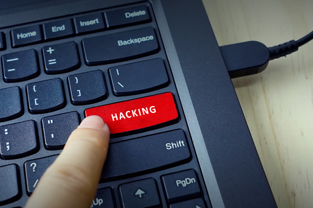 contextual: Close up of finger on keyboard button with HACKING word Stock Photo