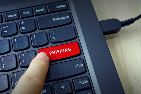 contextual: Close up of finger on keyboard button with PHISHING word