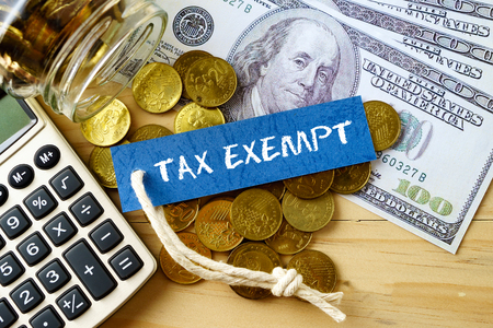 exempt: Finance conceptual image with TAX EXEMPT words, hundred dollar bills, golden coins and calculator on wooden background.