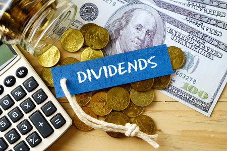 dividends: Finance conceptual image with DIVIDENDS words, hundred dollar bills, golden coins and calculator on wooden background.