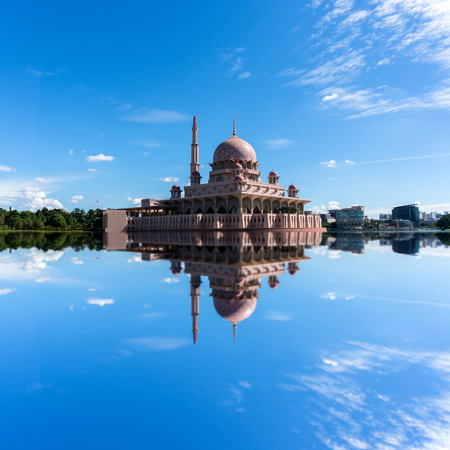 islamic scenery: Beautiful view of Putra Mosque in Putrajaya, Malaysia during a bright sunny day with full reflection. Stock Photo