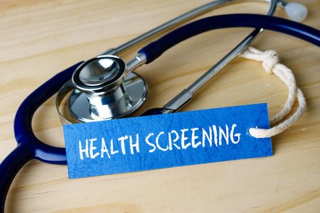 Medical conceptual image with HEALTH SCREENING words and stethoscope on wooden background.
