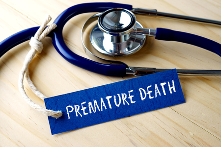 fractures: Medical conceptual image with PREMATURE DEATH word written on label tag and stethoscope on wooden background. Stock Photo