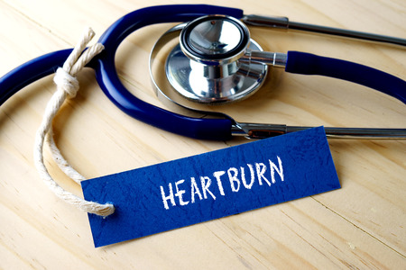 gastroenterology: Medical conceptual image with HEARTBURN word written on label tag and stethoscope on wooden background. Stock Photo