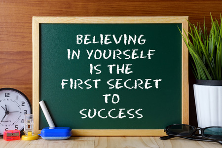 believing: Word quote BELIEVING IN YOURSELF IS THE FIRST SECRET TO SUCCESS written on green chalk board on wooden table.
