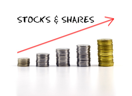 stocks and shares: Conceptual image. Stacks of coins against white background with red arrow and STOCKS & SHARES words. Stock Photo