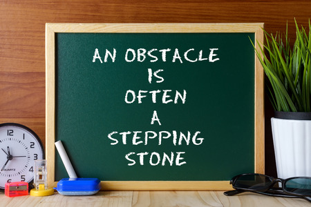 stepping stone: Word quote AN OBSTACLE IS OFTEN A STEPPING STONE written on green chalk board on wooden table.