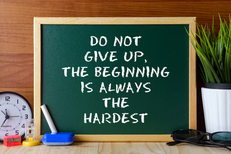 not give: Word quote DO NOT GIVE UP,THE BEGINNING IS ALWAYS THE HARDEST written on green chalk board on wooden table.