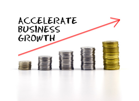 accelerate: Conceptual image. Stacks of coins against white background with red arrow and ACCELERATE BUSINESS GROWTH words.