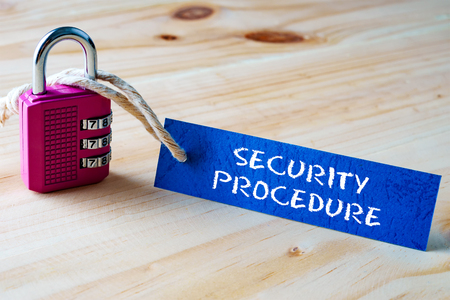 digitized: Words SECURITY PROCEDURE written on tag label tied with a padlock. Stock Photo