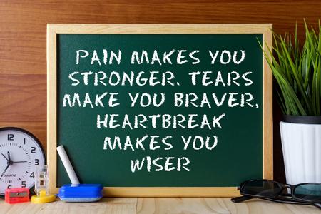 Woordcitaat PAIN maakt je sterker, TEARS JE moediger HEARTBREAK MAAKT U WISER geschreven op groene krijtbord op een houten tafel. Stockfoto