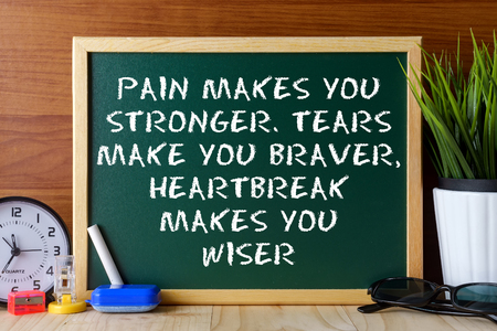 braver: Word quote PAIN MAKES YOU STRONGER,TEARS MAKE YOU BRAVER,HEARTBREAK MAKES YOU WISER written on green chalk board on wooden table. Stock Photo
